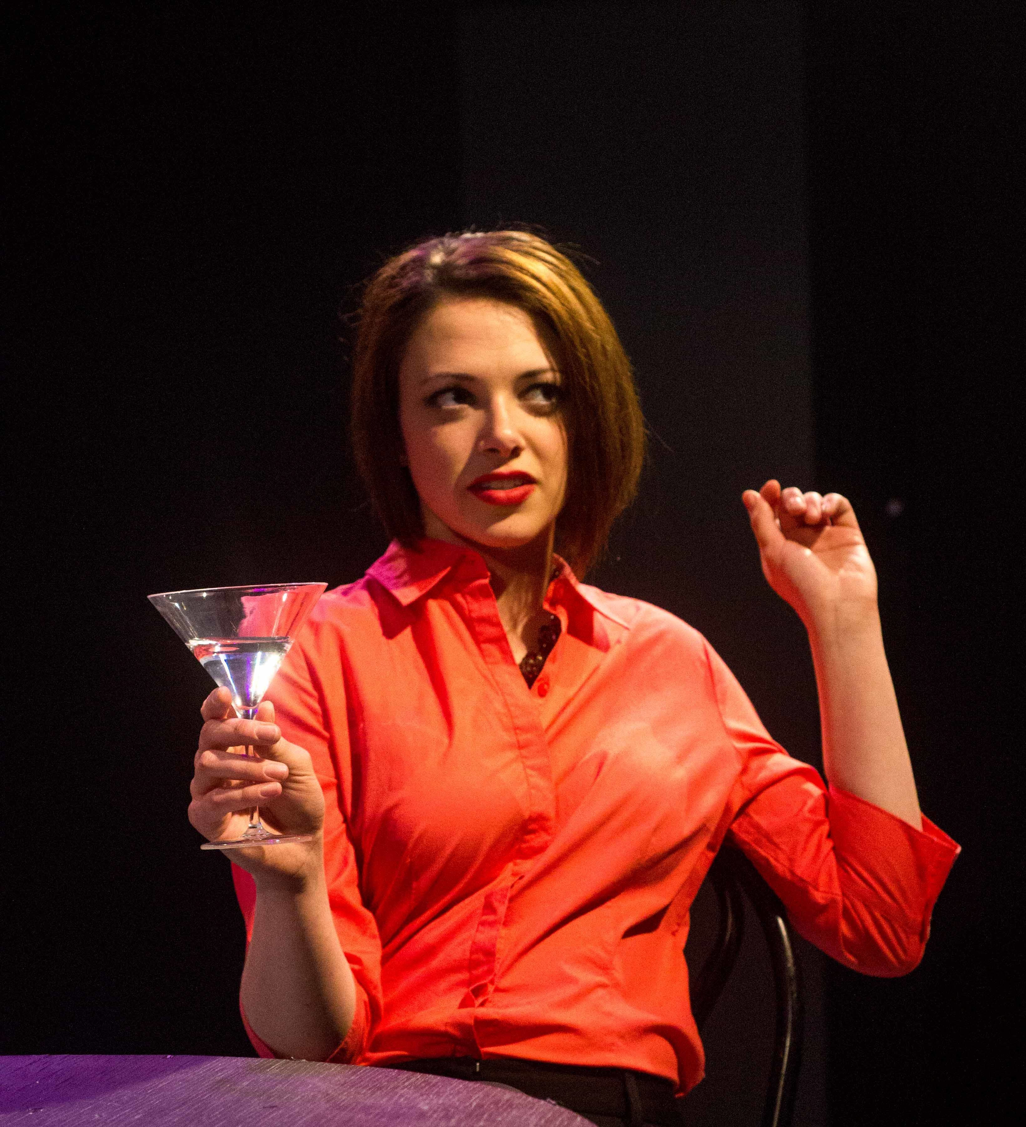 Emily Schultheis with a martini glass in the musical Island Song at the Bloomington Playwrights