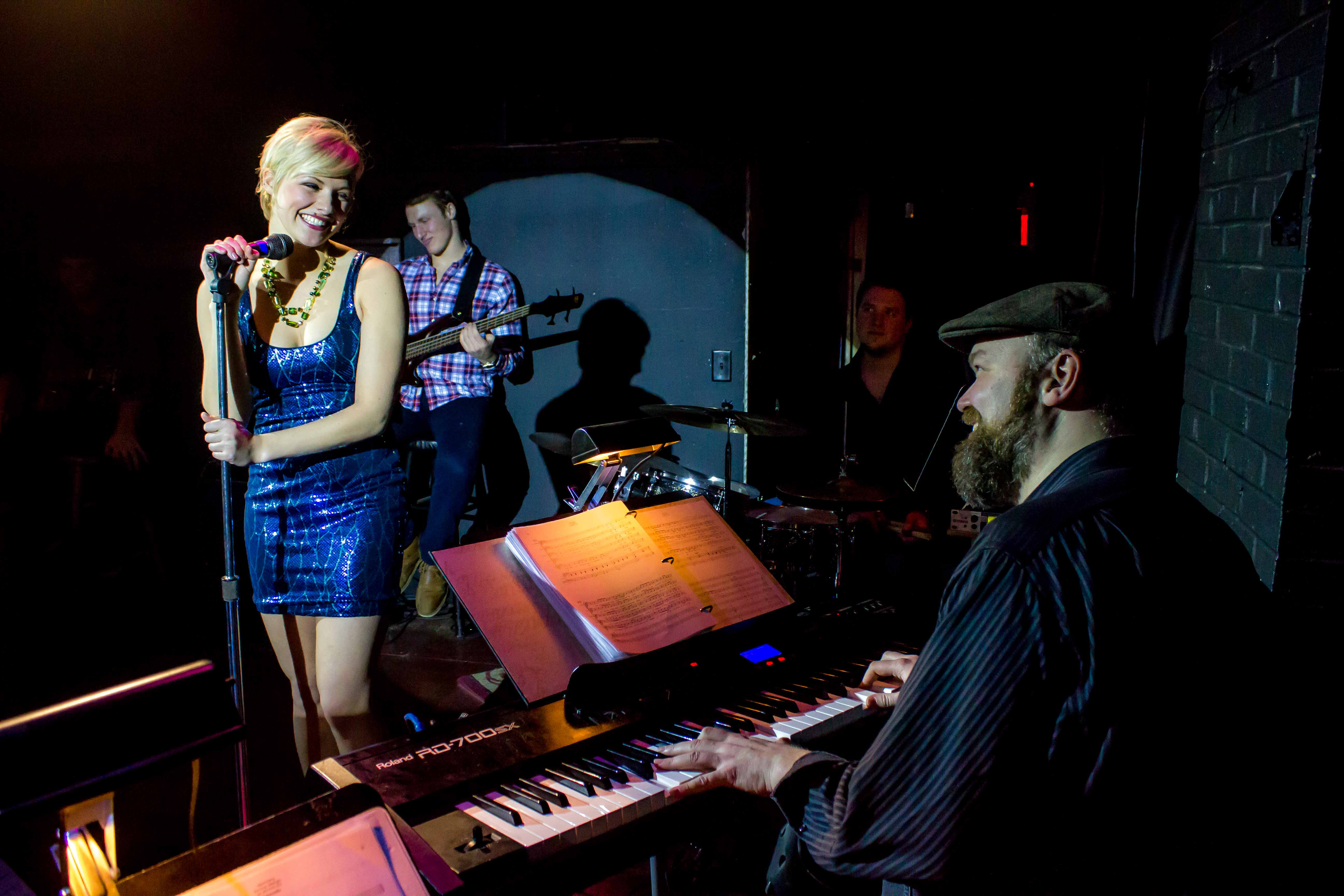 Kayla Eilers in a blue dress and Ray Fellman playing keyboard in the musical Island Song at the Bloomington Playwrights
